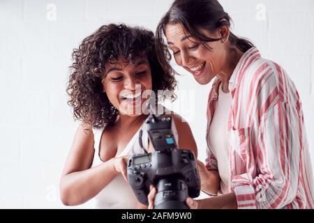 Lächelnd weibliche Fotograf Holding Kamera mit Modell im Studio Portrait Session - Stockfoto