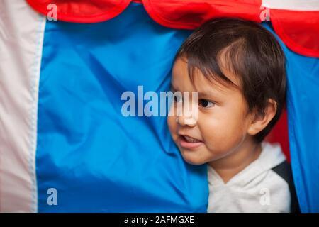 Das Gesicht der ein kleines Kind mit Wuscheligen Haaren, dazwischen der Eingang zu einem Spiel Zelt, die roten, weißen und blauen Farbtönen. - Stockfoto