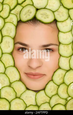 Junge schöne Frau mit Scheiben Gurken um ihr Gesicht posing - Stockfoto