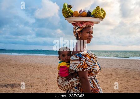 Ein gambischen Frau verkaufen frisches Obst am Strand mit ihrem Sohn auf dem Rücken. - Stockfoto