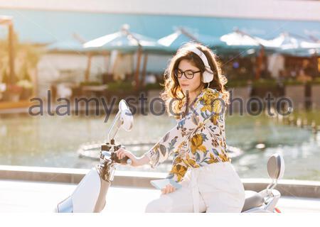 Anmutiges Mädchen mit eleganten Frisur sitzen auf Scooter neben Brunnen und genießen Lieblingssong. Portrait der Kuehlung Brünette junge Dame im eleganten Hosenanzug warten auf Freund zusammen zu fahren - Stockfoto
