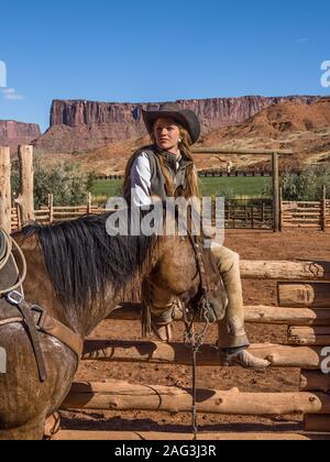 Eine junge attraktive Arbeitsbedingungen cowgirl Wrangler sitzt auf einem Holz Schiene Zaun von Ihrem Pferd auf einer Ranch in der Nähe von Moab, Utah. - Stockfoto