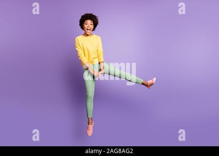 Volle Größe Foto fröhliche, lustige funky jugendlich afro-amerikanische Mädchen springen viel Spaß auf Herbst Wochenende freie Zeit tragen gelb Pullover grüne Hosen - Stockfoto