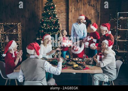 Merry X-Mas meeting fröhliche kleine Kinder reifen Rentner sitzen Tabelle mit Weihnachtsessen santa claus cap Hut mann Sack bag Geschenkset wollen - Stockfoto