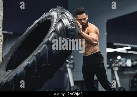 Shirtless muskulöse Kerl spiegeln große Reifen bei gym - Stockfoto