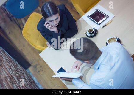 Zwei junge männliche und weibliche multirassischen Geschäftsleute arbeiten mit technischen Geräten an der Bar angeschlossen. Zwei junge kreative Mitarbeiter arbeiten wi - Stockfoto