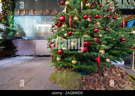Manchester, Großbritannien - 29 November 2019: Weihnachtsbaum am Eingang der Ivy Restaurant und der Brasserie in Neubaugebietes Spinningfields entfernt moderne developmen - Stockfoto