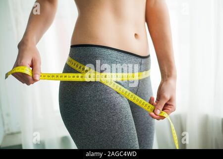 Hände messen Taille mit einem Band. Schlanke und gesunde Frau an ihrem Haus - Stockfoto