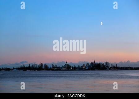Ersten Quartal Mond über die Ostsee nach Sonnenuntergang auf einem blauen Winter am Nachmittag. Aus South Harbor, Helsinki, Finnland gesehen; am Horizont, Valkosaari isl - Stockfoto