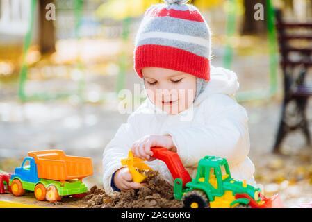 Das Kind spielt Autos, die in der Sandbox auf der Straße - Stockfoto