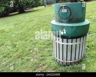 """Grüne Mülleimer mit tierischen Nachweis Deckel und die Worte """"Tonhöhe"""" neben dem Symbol einer Person fallen Müll in einem bin. Auf einem grasigen Hang - Stockfoto"""