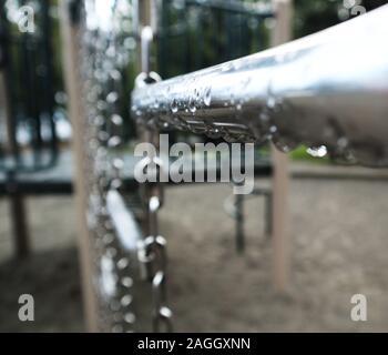 Wassertropfen auf eine Kletterwand, Bar und Kette. Leere Kinderspielplatz im Regen. - Stockfoto