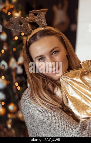 Fröhliche Frau empfangenen Geschenk zu Weihnachten, schöne Mädchen genießen gemütliche winter Eva im festlich dekorierten Haus mit Weihnachtsbaum, Frohes Neues Jahr - Stockfoto