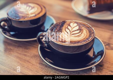 Zwei schwarze Tassen Kaffee mit Kunst auf einem Tisch, verschwommenes Wüste auf dem Hintergrund Stockfoto