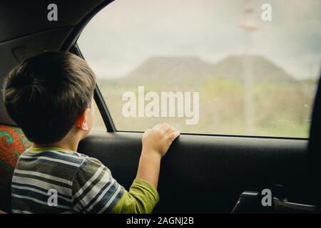 Kleiner Junge schaut durch das Fenster. Er reist auf einem Auto - Stockfoto