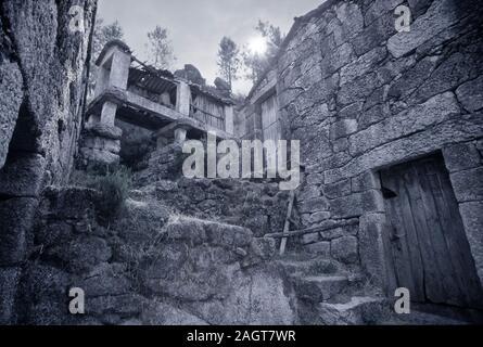 Ruine eines alten Land Landwirtschaft Haus und seine Getreidespeicher. Im Norden von Portugal. Farben Blau. Analog: 35-mm-Film. - Stockfoto