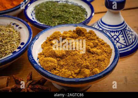 Gesundes Essen. Gewürze in Keramik Behälter typisch für Marokko auf einem alten Holztisch. Kurkuma, Kreuzkümmel, Sternanis, Dill und Thymian - Stockfoto