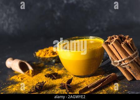 Golden Gelbwurz Milch auf dem dunklen Hintergrund mit Gewürzen Zimt und Zutaten - Stockfoto
