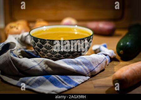Schüssel mit Suppe mit Gemüse um auf hölzernen Hintergrund - Stockfoto