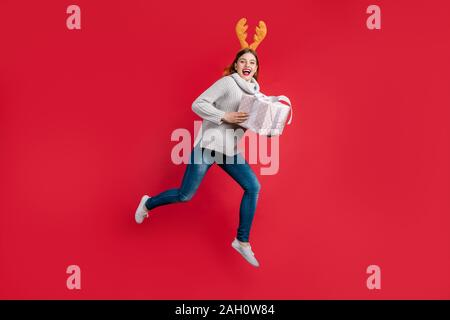 Funky Frau große Geschenkset santa Lieferung Tragen einer Kopfbedeckung, Hörner und Strickpullover isolierten roten Hintergrund - Stockfoto