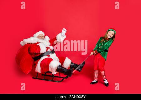 Volle Länge Foto des schönen zwei Märchen santa claus elf mit Haar graues Haar winken ziehen Schlitten Tasche tragen grüne mütze kopfbedeckung Brillen - Stockfoto