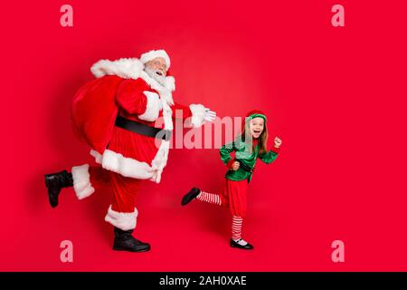 Full Body Profil Seite Foto von fröhlichen zwei Märchen Läufer santa claus elf in Hut Kopfbedeckung tragen von schweren Sack mit Geschenken auf Mitternacht tragen - Stockfoto