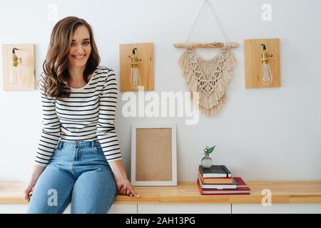 Junge fröhliche Frau sitzt auf einem Regal in einem Korridor, der nächsten Wand Lampen - Stockfoto