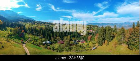Antenne Panoramablick auf eine ländliche Region mit Bauernhöfen, Feldern und die Karpaten Gebirge im Hintergrund. Borsa, Banat, Rumänien.