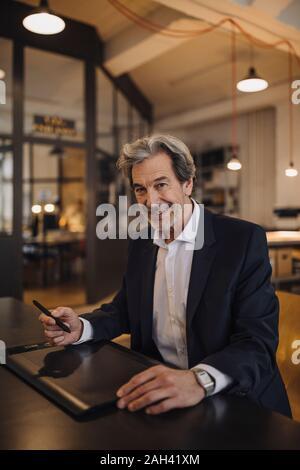 Portrait von lächelnden älteren Geschäftsmann mit grafiktablett am Schreibtisch im Büro - Stockfoto