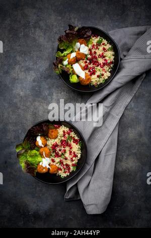 Schalen von falafel mit Salat, Joghurt, Granatapfel Samen, Petersilie, Minze und Tabbouleh Salat - Stockfoto