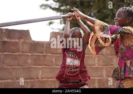 Zwei Kleine afrikanische Mädchen, Die An der Wasserpumpe Spielen - Stockfoto