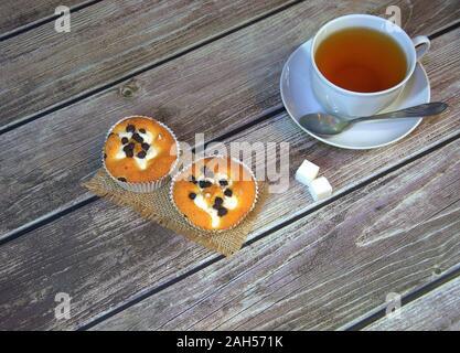 Weiße Keramik Tasse Tee auf eine Untertasse mit einem Löffel und einer Serviette mit zwei frischen Muffins und Würfel Zucker auf einen hölzernen Tisch. Close-up. - Stockfoto