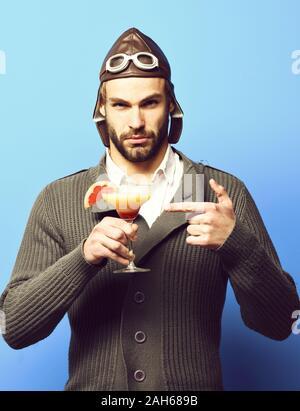 Schöne bärtige aviator Mann mit dem langen Bart auf ernstes Gesicht holding Glas alkoholfreien Cocktail in Grau in Form gestrickter Pullover mit Hut und Brille auf Blau studio Hintergrund - Stockfoto