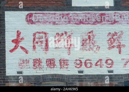 Eine Hand mit roter Schrift auf weißem Hintergrund mit chinesischen und westlichen Buchstaben und Zahlen gemalt, teilweise Ausradiert und übermalt - Stockfoto