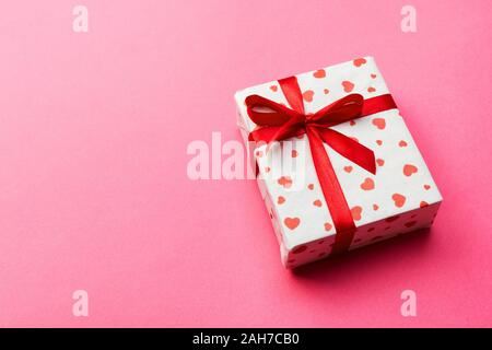 Geschenkbox mit roter Schleife und Herz auf rosa Hintergrund, Ansicht von oben mit der Kopie Platz für Text. - Stockfoto