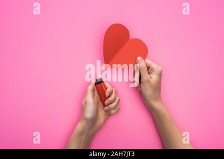 7/8-Ansicht von Frau Beleuchtung bis Leeres rotes Herz aus Papier mit leichter auf rosa isoliert - Stockfoto