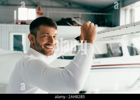 Lächelnd bärtigen Mann stand in der Nähe der Ebene und Sonnenbrille Holding - Stockfoto