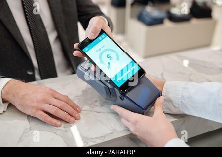 Die Hände der Jungen mobile Mann mit Smartphone während kontaktloses Bezahlen - Stockfoto