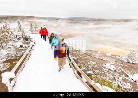 Touristen Spaziergang entlang eines schneebedeckten Promenade rund um das Porzellan Becken an der Norris Geyser Basin im Winter Dezember 20, 2019 im Yellowstone National Park, Wyoming. - Stockfoto