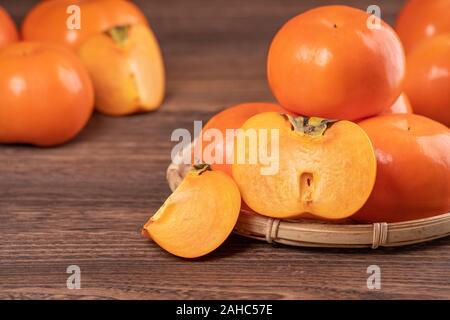 Frische, schöne orange Farbe kaki Kaki auf Bambus Sieb über dunklen Holztisch. Saisonale, traditionelle Frucht der chinesische Mondjahr, aus der Nähe. - Stockfoto