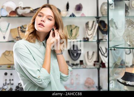 Portrait von fröhliches Mädchen, die versuchen, auf Ohrringe grün Stein in Schmuck Shop gemacht - Stockfoto