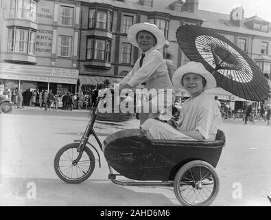 Vintage spätviktorianisches oder frühes Schwarz-Weiß-Foto von Edwardian, das einen jungen Jungen zeigt, der einen großen weißen Hut trägt, mit seiner Schwester ein Fahrrad trittend, einen Sonnenschirm oder einen Regenschirm hält und in einem Beiwagen sitzt, der am Fahrrad befestigt ist. Foto in Rhyl, nordwales. - Stockfoto