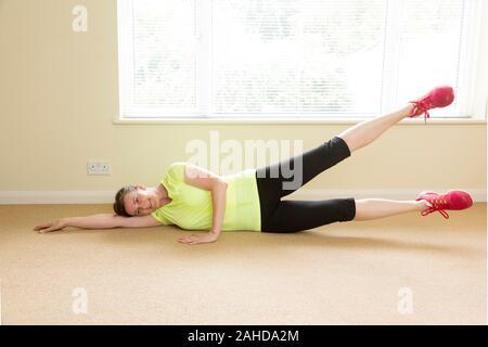 Frau Ausübung auf Ihrer Seite tun, Leg Lift Gesäß zu verbessern. - Stockfoto