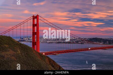 Panorama von der Golden Gate Bridge bei Sonnenuntergang mit Marin Headlands im Vordergrund, San Francisco Skyline und bunten Wolken im Hintergrund