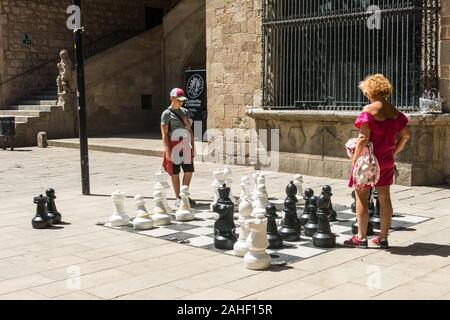 Barcelona, Spanien - 28. Juni 2019: eine Mutter und ihr Sohn spielen mit einem riesigen Schach auf dem Platz der alten mittelalterlichen Krankenhaus, im Viertel Raval, - Stockfoto