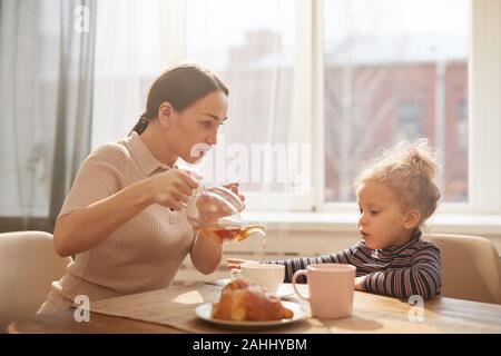 Seitenansicht Porträt des modernen Mutter gießen schwarzer Tee für süße kleine Mädchen beim Frühstück zu Hause sitzen gegen Fenster im Sonnenlicht