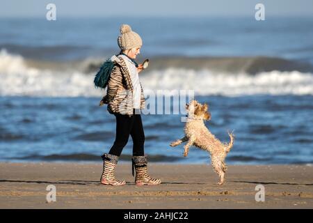Southport, Merseyside, zum 30. Dezember 2019. Ein junges Mädchen hat eine tolle Zeit beim Spielen mit Ihrem besten Freund am Strand in Southport, Merseyside. Strahlender Sonnenschein und blauer Himmel Besucher der Badeort begrüßt wie der milde Winter Wetter während der Weihnachtsferien fort. Credit: cernan Elias/Alamy leben Nachrichten - Stockfoto