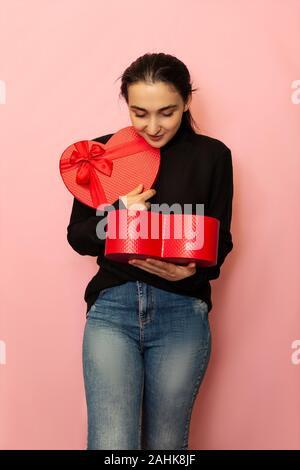 Erstaunt, überrascht, Frau hält herzförmigen Geschenkbox. Attraktive Mode Modell in Freizeitkleidung mit einem roten vorhanden, posieren. Valentinstag Geschenk - Stockfoto