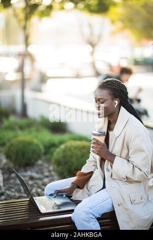 Ziemlich Afrikanische amerikanische Mädchen sitzt auf der Bank und Gespräch am Handy während der Arbeit am Laptop am Tisch sitzend mit Kaffee auf der Straße - Stockfoto