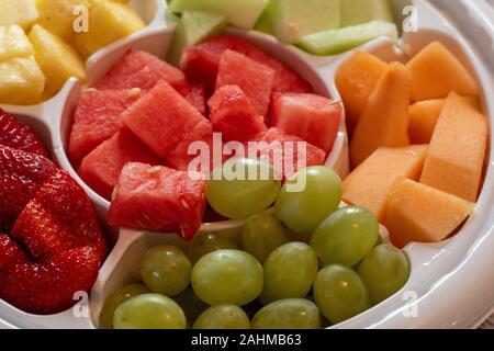 Eine Platte mit Obst, bestehend aus Wassermelonen, Honigmelonen, grüne Trauben, Erdbeeren, Ananas und Honigmelone ist in einem weißen Plastikschale serviert. - Stockfoto